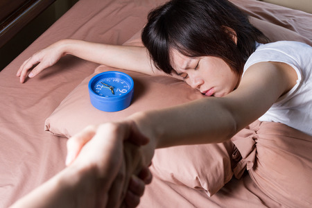 oversleep: woman oversleep and miss ringing of alarm clock with hand trying to drag her out of bed Stock Photo