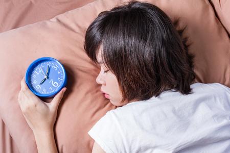 oversleep: woman oversleep and miss ringing of alarm clock Stock Photo