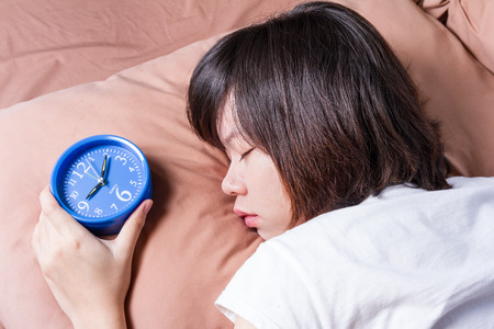 oversleep: woman oversleep and miss ringing of alarm clock Stock Photo