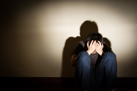 depresión: joven desesperado deprimida sentarse en el suelo ocultando el rostro, el efecto de viñeta Foto de archivo