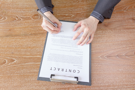 sign contract: business man signing contract document form Stock Photo