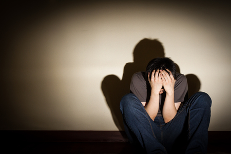 despaired: depressed despaired young man sit on the floor hiding his face, vignette effect Stock Photo