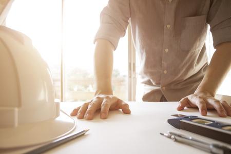 Ingenieur, der Architekturprojekt mit Technikwerkzeugen auf Schreibtisch im Büro zeichnet und plant