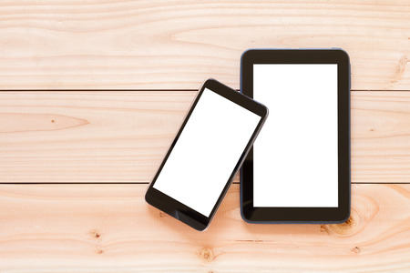 top view of tablet computer and mobile phone with blank screen on wooden background Stockfoto