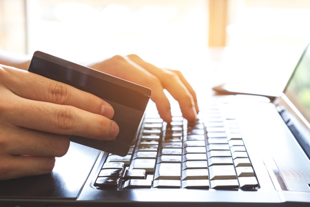 man hand holding credit card and using laptop computer for online shopping