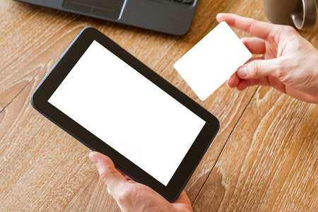 hand holding credit card and using tablet computer with blank white screen for online shopping