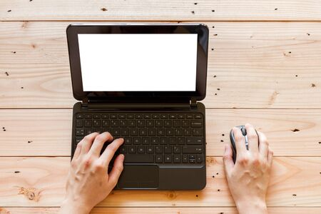 man hand using laptop computer with blank screen on wooden background, top view
