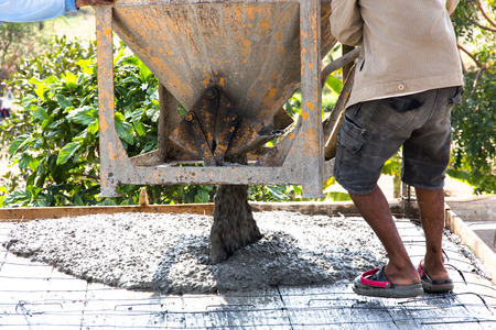 rigger: Pouring concrete on the ground using a crane with a bucket Stock Photo