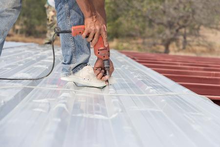 Man aan het werk op het dak van het metaal kaas in bouwplaats