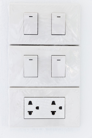 switch plug: Home standard electrical switch and plug on wall Stock Photo