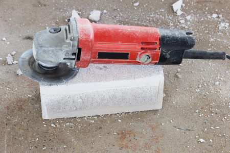 specialists: Home building wall cutting bricks in construction sites by using the tool specialists. Stock Photo