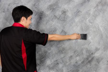 plasterwork: man work hand holding tool painting wall Loft style