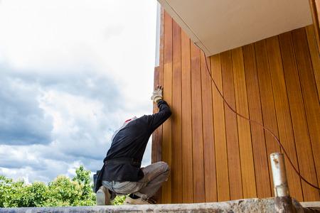 Men build siding Fiber Cement Board on wall exterior Stockfoto