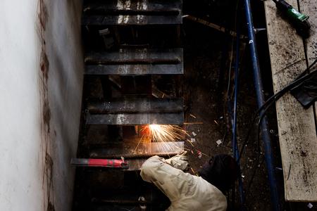 Men work welding Installation of steel stairs using steel i-beams.