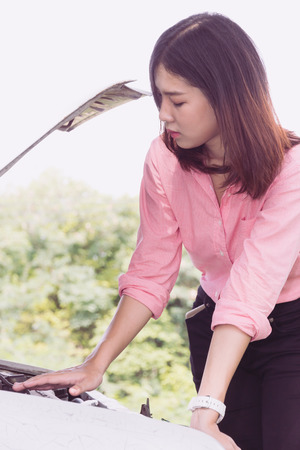 Woman with broken car on the road waiting for help.