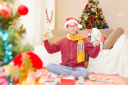 Young man showing cheerful gestures with happy presents on Christmas Eve. In his home