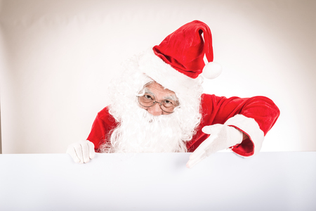 Merry christmas,Santa Claus pointing in white blank sign Stock Photo