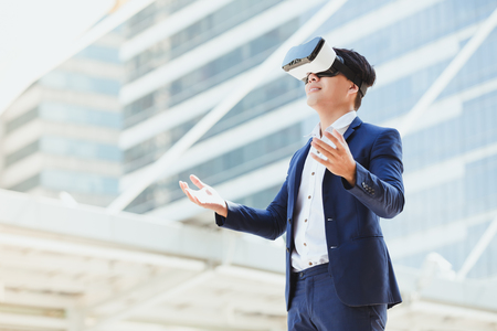 Concept simulation technology business,Businessman in glasses virtual reality with city town background