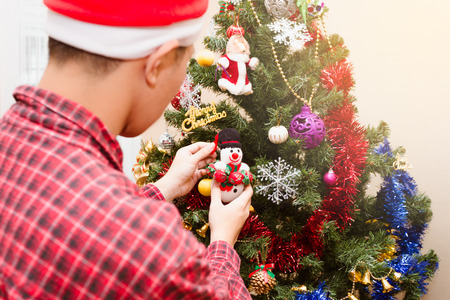 Young men decoration Christmas Tree  Welcome to the coming holidays. Stock Photo