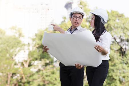 asian men and women engineers work on plans construction  in the park