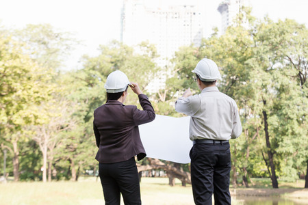 Asian man and woman engineers work on plans construction in the park