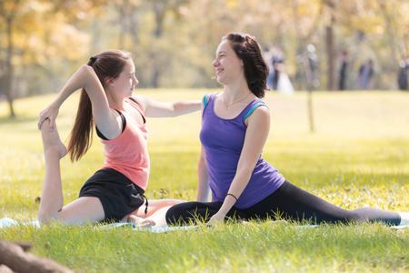 Sisters  doing yoga pose meditation in the public park Reklamní fotografie