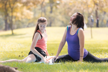 Holiday my Sisters  doing yoga pose meditation in the public park Sport Healthy concept.