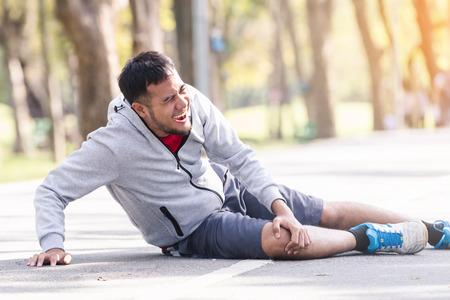 Azjatycki młody sportowiec kontuzji kolana po joggingu Zdjęcie Seryjne