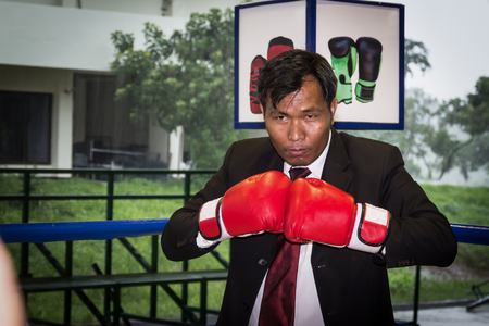 Asian businessman with boxing gloves. Concept of relentless struggle and success Stock Photo