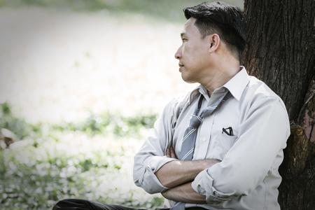 Asian business man failing and serious under tree in the park