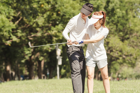 Asian couple playing golf. man teaching woman to play golf while standing on field Stock Photo