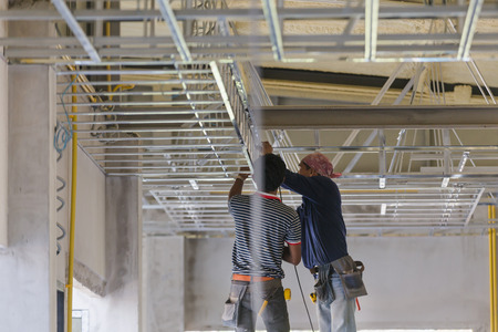 Construction worker ceiling metal frame with screwdriver for interior build gypsum board ceiling