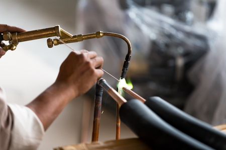 An industry worker welds to join the copper pipe of an air conditioner