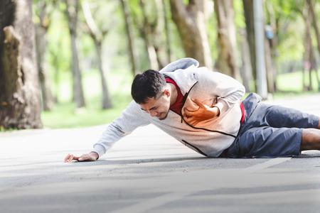 Asian cardiac arrest running young man heart attack in park.Severe heartache