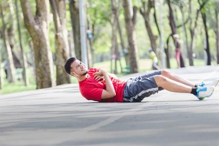 Arrêt cardiaque asiatique en cours d'exécution de crise cardiaque jeune homme dans le parc.