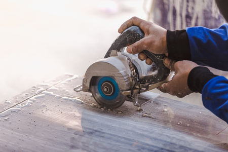 Man professional worker cutting tile with circular saw electric construction interior. Stockfoto