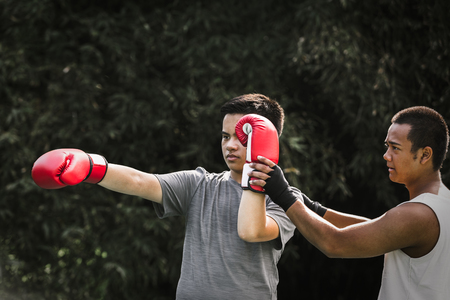 Asian young men with personal trainer boxing friend, Boxing gloves