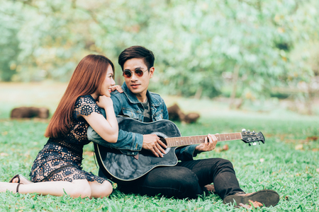 Asian couple in love playing acoustic song  guitar sitting on grass in the park