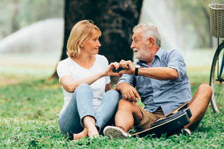 Senior couple in love show hand made heart shaped icon sitting on grass in the park