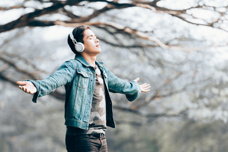 Asian young men stand arms up in nature, listen to music with headphones.
