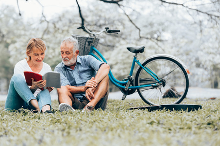Senior couple in love sitting reading book on grass in the park