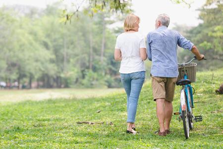 Ältere Paare , die ihr Fahrrad entlang glückliche Unterhaltung gehen Standard-Bild