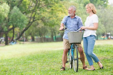 Senior couple walking their bike along happily talking happily. Stockfoto