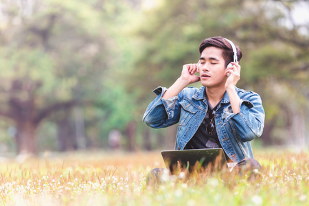 Asian young men sitting on nature listen to music with headphone