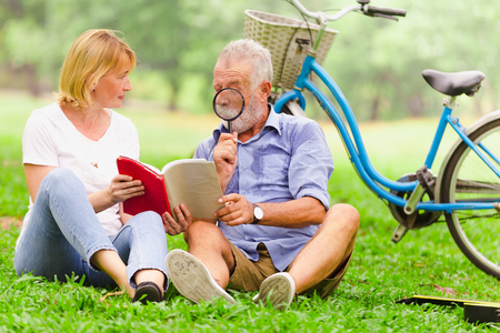 Senior couple in love sitting reading book with magnifying glass on grass in the park Stock Photo