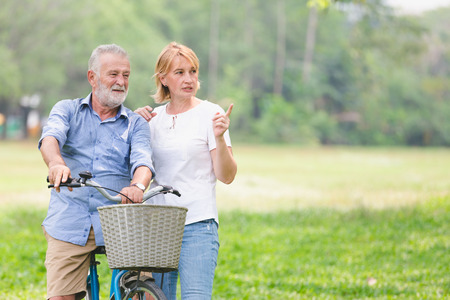 Senior couple walking their bike along happily talking happily. Stock Photo