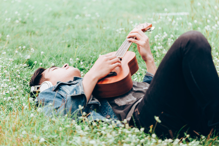 Asian young men lie about on nature listen to music with headphone and play ukulele