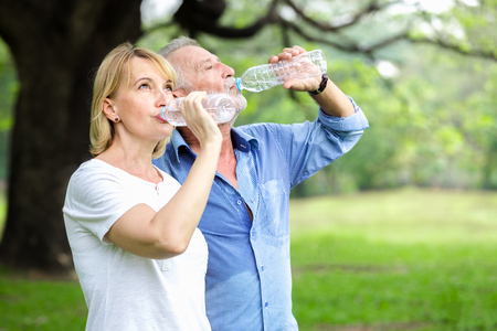Portrait senior couple debout eau potable dans le parc Banque d'images - 96513323