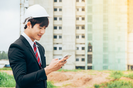 Asian engineer holding smartphone work concept teamwork of building construction. Project contractor reviewing plan work in construction site.