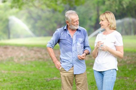 Portrait senior couple standing drinking water at the park